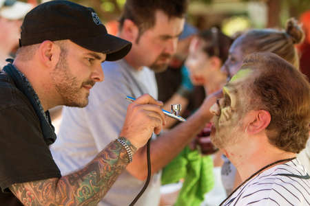 repugnant: Atlanta, GA, USA - July 25, 2015:  Makeup artists give participants zombie makeovers before the start of the Atlanta Zombie Pub Crawl in Atlanta, GA on July 25, 2015. Editorial
