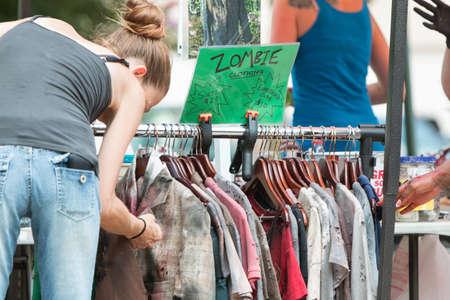 hanging woman: Atlanta, GA, USA - July 25, 2015:  A woman looks over a rack of torn and bloody zombie clothing before the Atlanta Zombie Pub Crawl in Atlanta, GA.