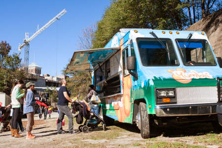 delicious food: Atlanta, GA, USA - November 14, 2015:  People stand in line to order from a popular food truck at an Atlanta fall festival.