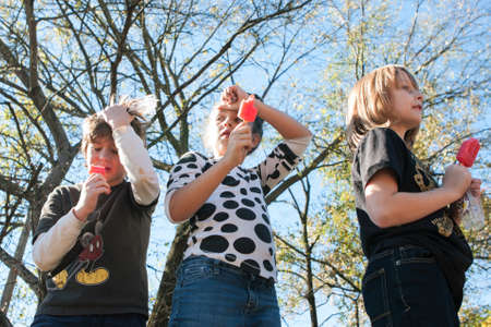 Atlanta, GA, USA - November 14, 2015:  Kids hold their heads as they experience brain freeze while competing in a popsicle eating contest at the King of Pops Festival in Atlanta, GA on November 14, 2015.