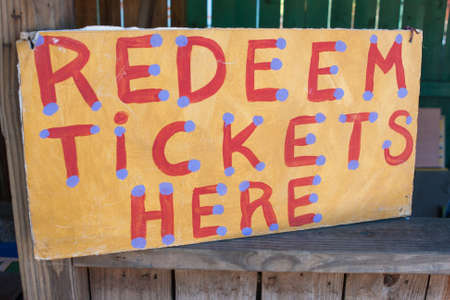 happening: Handmade sign reading Redeem Tickets Here sits at booth of carnival.