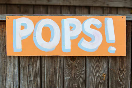 grassroots: Handmade sign reads Pops! at grassroots carnival.