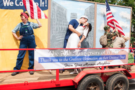 Alpharetta, GA, USA - August 1, 2015:  A parade float with live characters pays tribute to Rosie Rivoter, the Times Square kiss and the Iwo Jima flag planting to commemorate the 70th anniversary of World War II at the Old Soldiers Day Parade. Editorial
