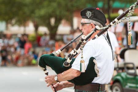 gaita: Alpharetta, GA, EE.UU. - 1 de agosto de 2015: Un hombre mayor que toca la gaita antes del inicio del desfile anual del Día viejos soldados en Alpharetta, GA el 1 de agosto de 2015.