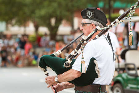gaita: Alpharetta, GA, USA - August 1, 2015:  A senior man plays the bagpipes before the start of the annual Old Soldiers Day Parade in Alpharetta, GA on August 1, 2015.