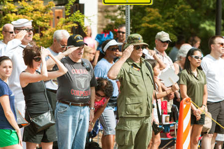 fatigues: Alpharetta, GA, USA - August 1, 2015:  Combat veterans attending the annual Old Soldiers Day parade salute the American flag as it passes by, on August 1, 2015 in Alpharetta, GA. Editorial