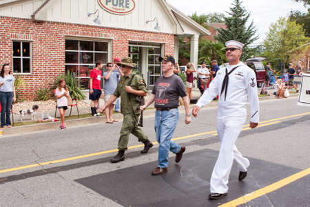 fatigues: Alpharetta, GA, USA - August 1, 2015:  Three combat veterans representing the Army, Navy and Marines walk in the annual Old Soldiers Day Parade in Alpharetta, GA on August 1, 2015.