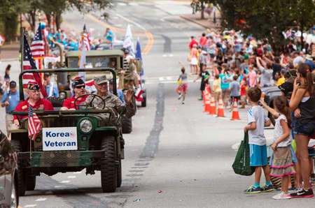fatigues: Alpharetta, GA, USA - August 1, 2015:  A Korean War veteran driving an army jeep waves to spectators attending the annual Old Soldiers Day Parade in Alpharetta, GA on August 1, 2015. Editorial