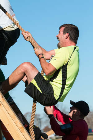 struggles: Buford, GA, USA - November 21, 2015:  A man struggles to use a rope to climb up a wall at one of the obstacles at the Muddy Brute Challenge in Buford, GA on November 21, 2015. Editorial