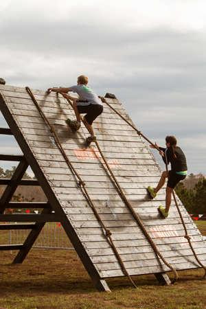 adrenaline rush: Buford, GA, USA - November 21, 2015:  A young woman and man climb up a wall obstacle using ropes at the Muddy Brute Challenge in Buford, GA on November 21, 2015.