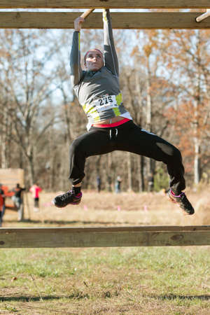 'pull over': Buford, GA, USA - November 21, 2015:  A young woman grips a metal bar as she tries to pull herself across an obstacle while suspended over the ground, at the Muddy Brute Challenge in Buford, GA on November 21, 2015.