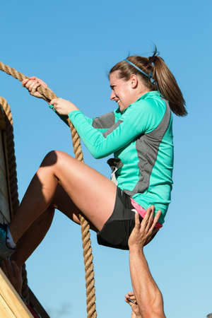 struggles: Buford, GA, USA - November 21, 2015:  A woman struggles to use a rope to climb up a wall at one of the obstacles at the Muddy Brute Challenge in Buford, GA on November 21, 2015. Editorial