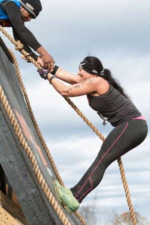 adrenaline rush: Buford, GA, USA - November 21, 2015:  A woman struggles to climb up a wall obstacle using a rope at the Muddy Brute Challenge in Buford, GA on November 21, 2015.