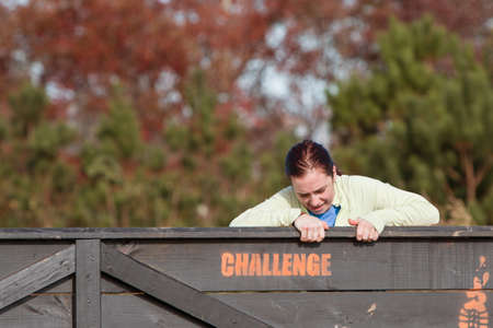 struggles: Buford, GA, USA - November 21, 2015:  A young woman struggles to climb over a wooden wall obstacle at the Muddy Brute Challenge race in Buford, GA on November 21, 2015.
