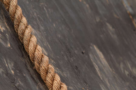 Closeup of thick rope lying against wooden wall at extreme obstacle course race. Stock Photo