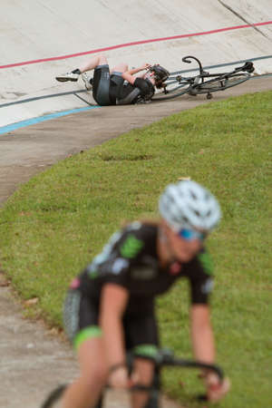 velodrome: East Point, GA, USA - August 29, 2015:  A female pro cyclist lies on the track after crashing in a race at the Dick Lane Velodrome on August 29, 2015 in East Point, GA.