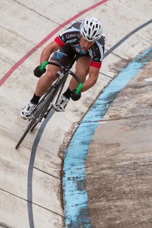 East Point, GA, USA - August 29, 2015:  A pro cyclist sprints during his time trial at the Dick Lane Velodrome in East Point, GA on August 29, 2015.