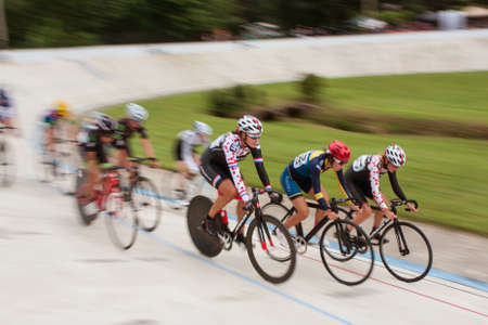 East Point, GA, USA - August 29, 2015:  A group of female pro cyclists motion blur while competing in a race at the Dick Lane Velodrome in East Point, GA on August 29, 2015.