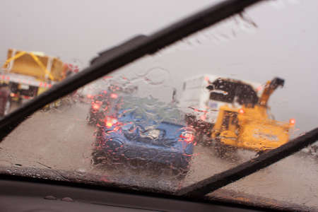 hydroplaning: A cars windshield wipers work to displace heavy rain causing impaired vision during a thunderstorm in Atlanta rush hour traffic. Stock Photo