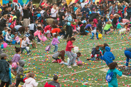 cordoned: Marietta, GA, USA - March 26, 2016:  Kids and parents eagerly dash out onto the football field at the start of a massive community Easter egg hunt at Sprayberry High School on March 26, 2016 in Marietta, GA.