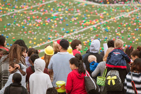 Marietta, GA, USA - March 26, 2016:  Children and families stand waiting for the start of a massive community Easter egg hunt on the football field of Sprayberry High School on March 26, 2016 in Marietta, GA.