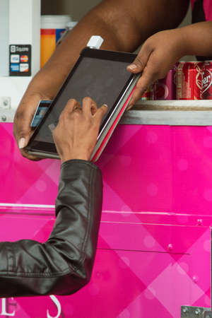comtemporary: Marietta, GA, USA - March 26, 2016:  A woman signs a digital tablet with her finger in a food truck credit card transaction at an event on March 26, 2016 in Marietta, GA.