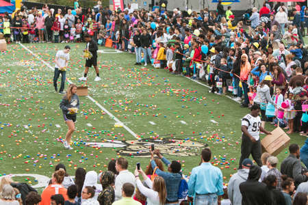 cordoned: Marietta, GA, USA - March 26, 2016:  Teen volunteers cover a high school football field with plastic easter eggs and candy, as hundreds of local residents wait to begin a massive community easter egg hunt at Sprayberry High School on March 26, 2016 in Mar
