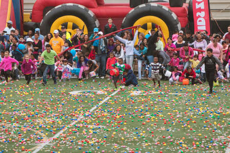 cordoned: Marietta, GA, USA - March 26, 2016:  Children and parents eagerly dash out onto the football field at Sprayberry High School for the start of a massive community Easter egg hunt on March 26, 2016 in Marietta, GA.