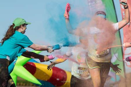 adrenaline rush: Hampton, GA, USA - April 2, 2016:  Volunteers douse runners with colored corn starch at The Color Run on April 2, 2016 in Hampton, GA.
