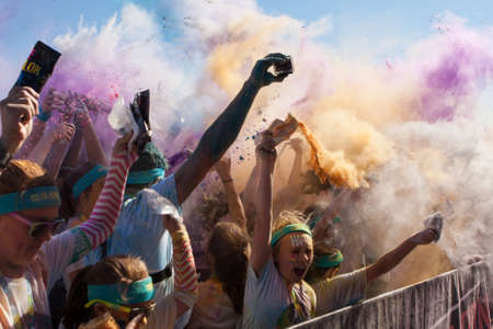 adrenaline rush: Hampton, GA, USA - April 2, 2016:  A crowd of runners who completed the Color Run, toss packets of colored corn starch into the air, creating an organic explosion of colors over the group on April 2, 2016 in Hampton, GA.