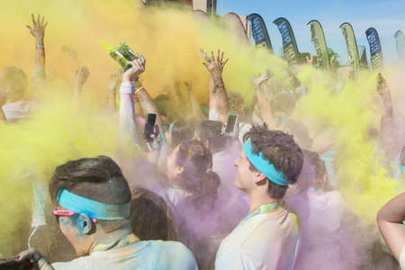 adrenaline rush: Hampton, GA, USA - April 2, 2016:  Runners who completed the Color Run toss packets of colored corn starch into the air, creating an organic explosion of colors over the group on April 2, 2016 in Hampton, GA.