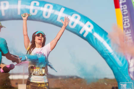 adrenaline rush: Hampton, GA, USA - April 2, 2016:  A woman extends her arms in jubilation as shes doused with colored corn starch at The Color Run on April 2, 2016 in Hampton, GA.