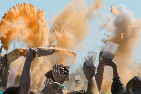 adrenaline rush: Hampton, GA, USA - April 2, 2016:  Peoples hands toss packets of colored corn starch in the air to create a color explosion at the Color Run on April 2, 2016 in Hampton, GA.