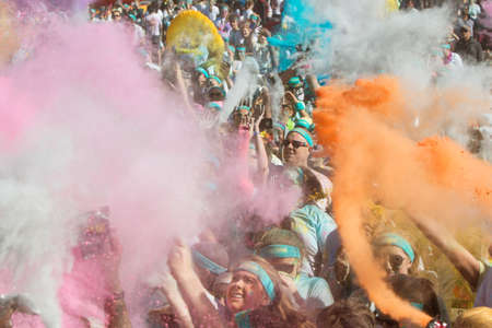 adrenaline rush: Hampton, GA, USA - April 2, 2016:  A huge crowd of runners who completed the Color Run, toss packets of colored corn starch into the air, creating an organic explosion of colors over the group on April 2, 2016 in Hampton, GA.