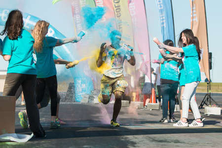 adrenaline rush: Hampton, GA, USA - April 2, 2016:  A runner gets squirted with multiple colors of corn starch at The Color Run on April 2, 2016 in Hampton, GA.