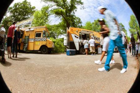 Atlanta, GA, USA - April 16, 2016:  People motion blur in a circular fisheye scene as they walk past food trucks lined up in Grant Park at the Food-o-rama festival on April 16, 2016 in Atlanta, GA.