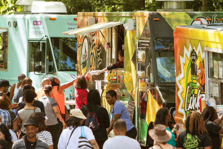 Atlanta, GA, USA - April 16, 2016:  A crowd of people buy meals from food trucks lined up in Grant Park at the Food-o-rama festival on April 16, 2016 in Atlanta, GA. 新聞圖片