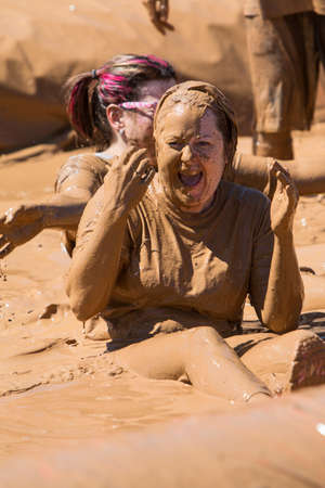 mud pit: Hampton, GA, USA - April 23, 2016:  A woman covered in mud laughs after sliding into a pit of muddy water at the Dirty Girl Mud Run obstacle course event on April 23, 2016 in Hampton, GA.