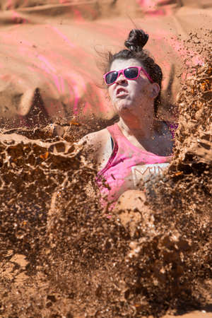 mud pit: Hampton, GA, USA - April 23, 2016:  A woman creates a huge splash of muddy water as she lands in a mud pit at the Dirty Girl Mud Run obstacle course event on April 23, 2016 in Hampton, GA.