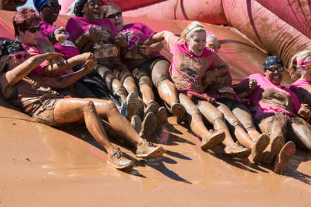 Hampton, GA, USA - April 23, 2016:  A group of muddy women hold hands as they slide down toward a mud pit at the Dirty Girl Mud Run obstacle course event on April 23, 2016 in Hampton, GA. Editorial