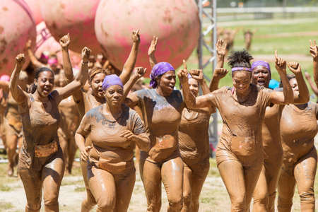 exhilerating: Hampton, GA, USA - April 23, 2016:  A group of muddy women celebrate with raised arms as they jog toward the finish line of the Dirty Girl Mud Run obstacle course event on April 23, 2016 in Hampton, GA.