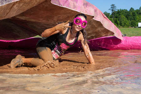 mud pit: Hampton, GA, USA - April 23, 2016:  A woman flashes a peace sign as she splashes and crawls through muddy water at the Dirty Girl Mud Run obstacle course event on April 23, 2016 in Hampton, GA. Editorial