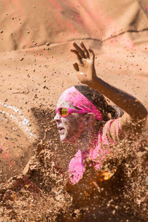 Hampton, GA, USA - April 23, 2016:  A woman splashes muddy water as she lands in a mud pit at the Dirty Girl Mud Run obstacle course event on April 23, 2016 in Hampton, GA.