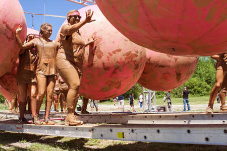 Hampton, GA, USA - April 23, 2016:  Women try to keep their balance as they dodge large rubber balls at one of the obstacles at the Dirty Girl Mud Run obstacle course event on April 23, 2016 in Hampton, GA.