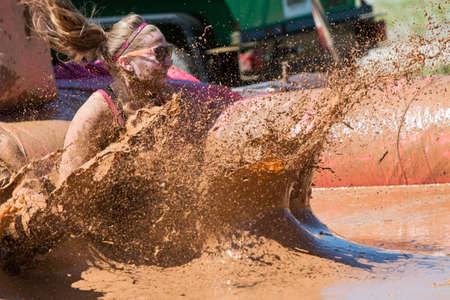 mud pit: Hampton, GA, USA - April 23, 2016:  A woman creates a large splash of muddy water as she lands in a mud pit at the Dirty Girl Mud Run obstacle course event on April 23, 2016 in Hampton, GA.