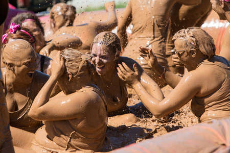 mud pit: Hampton, GA, USA - April 23, 2016:  A group of muddy women splash each other with muddy water after sliding into a mud pit at the Dirty Girl Mud Run obstacle course event on April 23, 2016 in Hampton, GA.