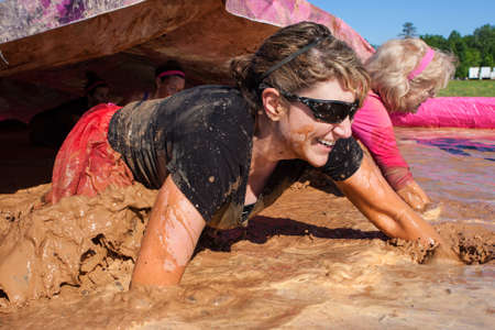 Hampton, GA, USA - April 23, 2016:  Women splash and crawl through muddy water at the Dirty Girl Mud Run obstacle course event on April 23, 2016 in Hampton, GA.