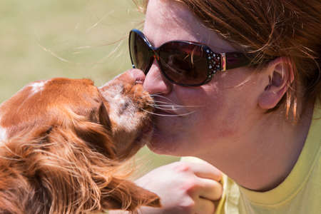 smooching: Snellville, GA, USA - May 14, 2016:  A young woman and her dog compete in a kissing contest at Pawfest, a dog festival on May 14, 2016 in Snellville, GA. Editorial