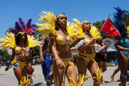 arousing: Atlanta, GA, USA - May 28, 2016:  Women wearing yellow bikinis and elaborate feathered costumes walk in a parade to celebrate Caribbean culture on North Avenue on May 28, 2016 in Atlanta, GA. Editorial