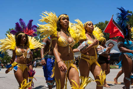 Atlanta, GA, USA - May 28, 2016:  Women wearing yellow bikinis and elaborate feathered costumes walk in a parade to celebrate Caribbean culture on North Avenue on May 28, 2016 in Atlanta, GA. Editorial